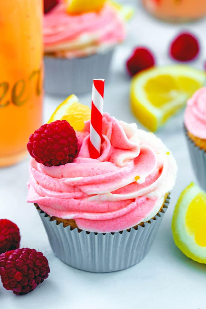 Head-on view of a raspberry lemonade cupcake with swirled frosting, straw, and raspberries and lemon wedges all around with more cupcakes in background