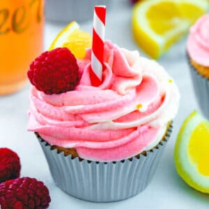 View of a raspberry lemonade cupcake with raspberry, lemon wedge, and straw garnish with raspberries and lemons in background