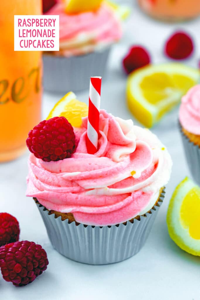 Head-on view of a raspberry lemonade cupcake with swirled frosting, straw, and raspberries and lemon wedges all around with more cupcakes in background and recipe title at top