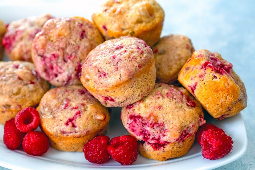 Landscape view of a white platter filled with raspberry, mango, ginger muffins piled up with lots of fresh raspberries scattered around