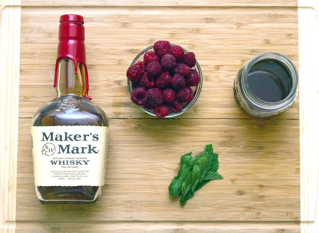 Overhead view of ingredients used in raspberry whiskey cocktail, including Maker's Mark whisky, raspberries, mint leaves, and vanilla simple syrup