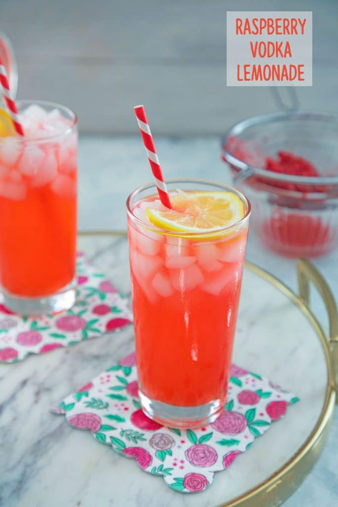 "Head-on view of 2 glasses of raspberry vodka lemonade on flowered napkins and a marble surface with raspberries in strainer in background and ""Raspberry Vodka Lemonade"" text at top"