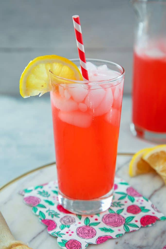 An up-close head-on view of a tall glass of raspberry vodka lemonade on a flowered napkin with a red and white striped straw and a lemon wedge garnish and a pitcher of more lemonade in the background