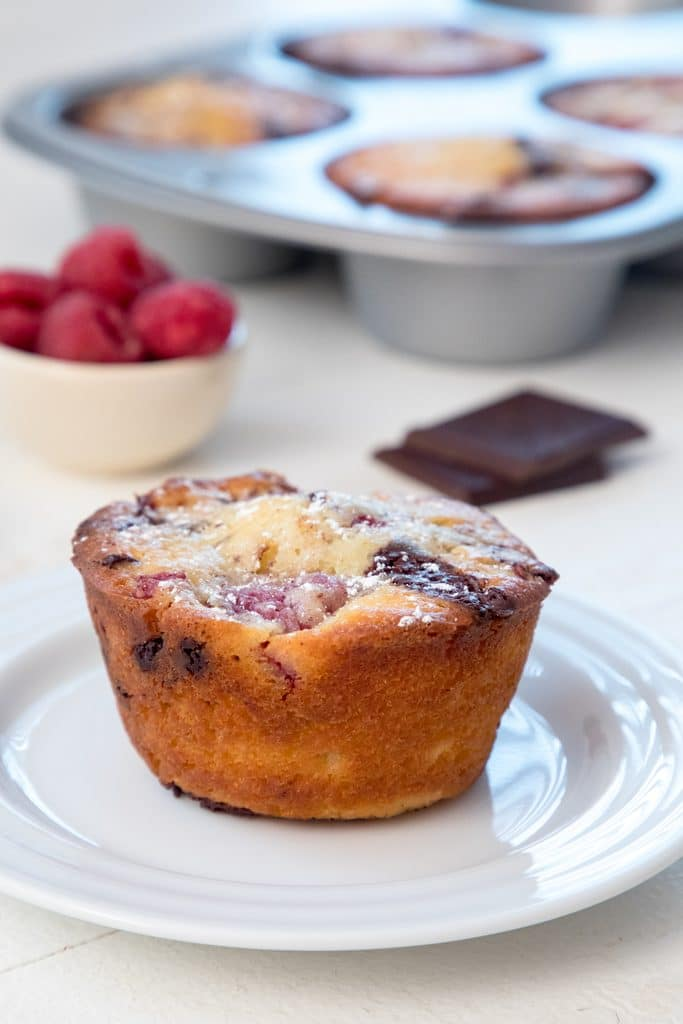 Head-on view of a raspberry dark chocolate muffin on a white plate with dark chocolate squares, bowl of raspberries, and tin with more muffins in the background