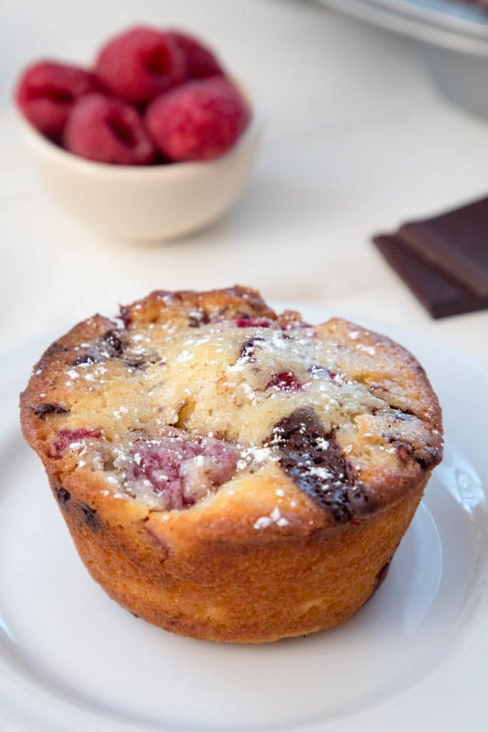 Overhead closeup view of a raspberry dark chocolate muffin with dark chocolate squares and bowl of raspberries in background