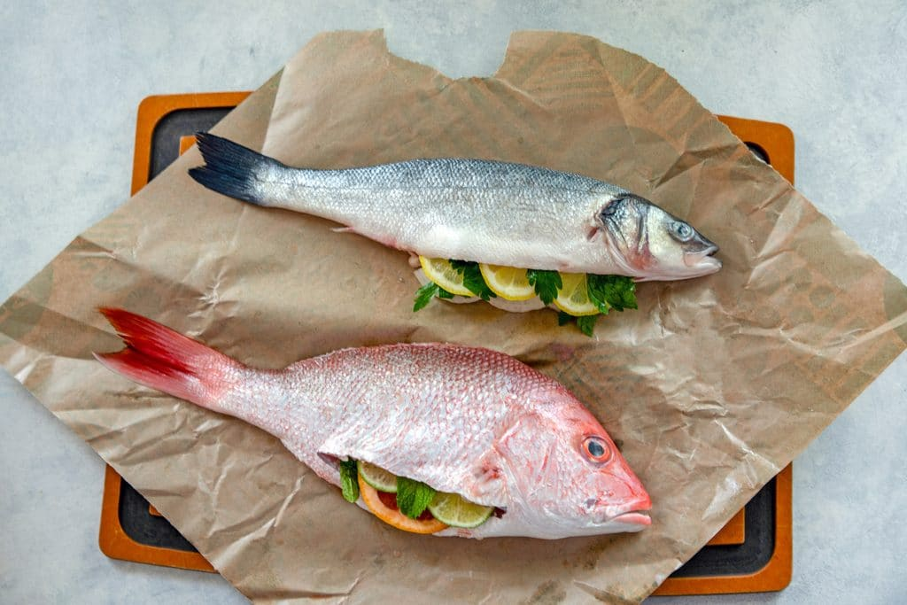 Overhead view of whole branzino and whole red snapper stuffed with herbs and citrus on parchment paper
