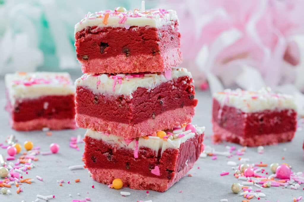 Landscape photo of stack of three red velvet cookie dough bars with white chocolate ganache and Valentine's Day sprinkles with more cookie dough bars and sprinkles all around.