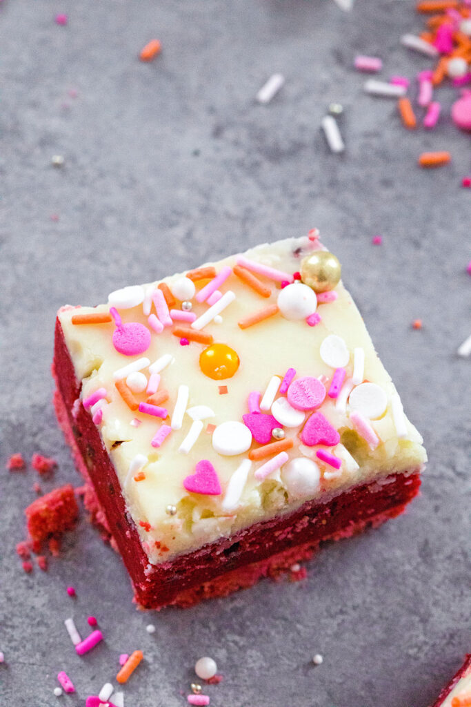 Overhead view of a red velvet cookie dough bar topped with white chocolate ganache with Valentine's Day sprinkles.