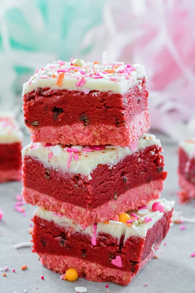 Head-on view of a stack of three red velvet cookie dough bars with white chocolate ganache topping and Valentine's Day sprinkles with sprinkles all around.