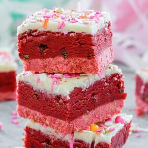 Head-on view of a stack of three red velvet cookie dough bars with white chocolate ganache topping and Valentine's Day sprinkles with sprinkles all around