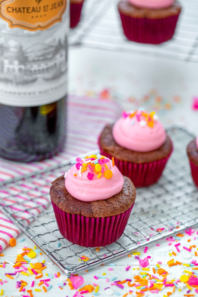 Head-on view from a distance of red wine cupcakes on a cooling rack with pink frosting and sprinkles with bottle of wine, more cupcakes, and sprinkles in background