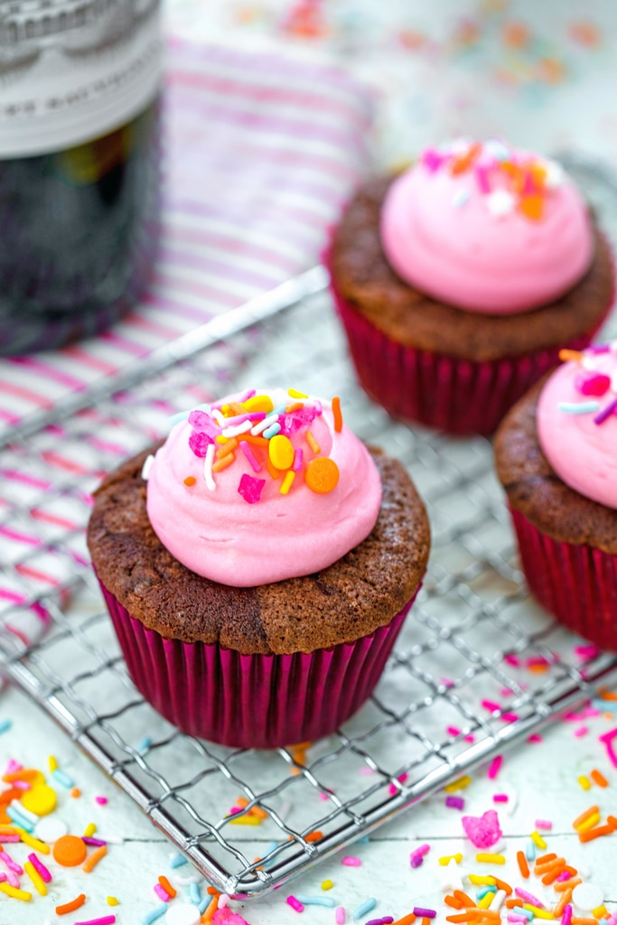 Head-on view of a red wine cupcake with pink frosting and sprinkles on a baking rack with more cupcakes and sprinkles in the background