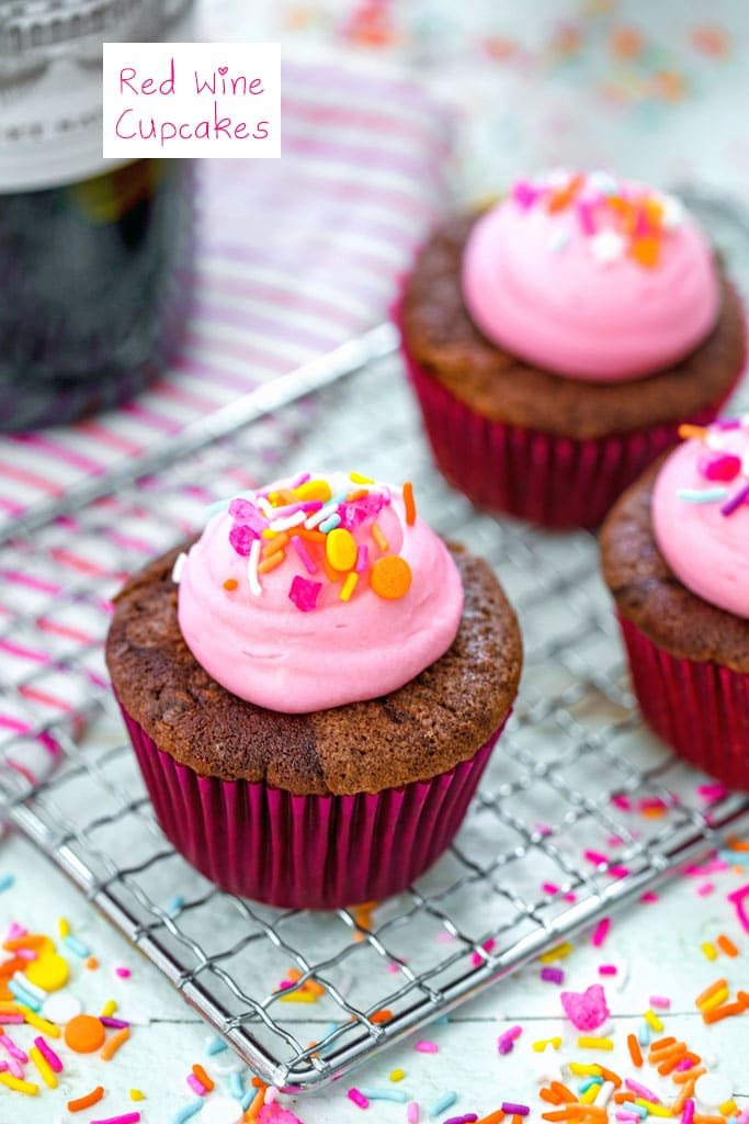 Head-on view of a red wine cupcake with pink frosting and sprinkles on a baking rack with more cupcakes and sprinkles in the background with recipe title at top