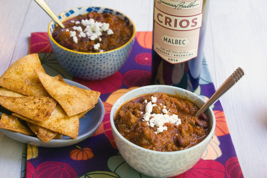Overhead view of a bowl of red wine pumpkin chili topped with feta cheese with bottle of red wine, second bowl of chili, and homemade tortilla chips in background