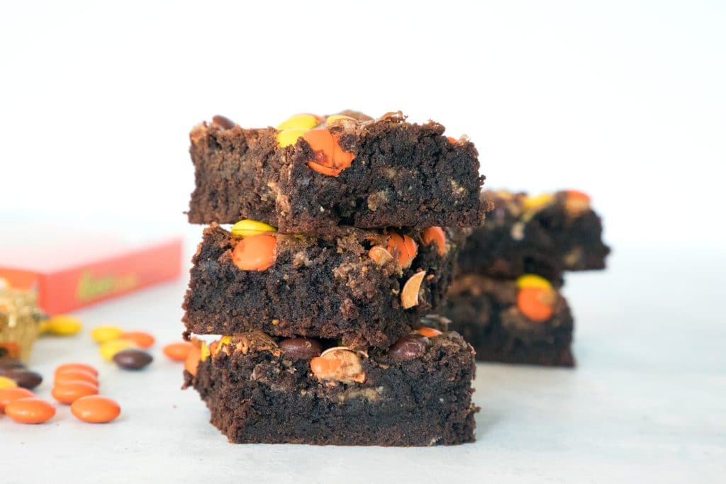 Landscape head-on view of stack of three chocolate Reese's Pieces peanut butter brownies with Reese's Pieces and more brownies in background