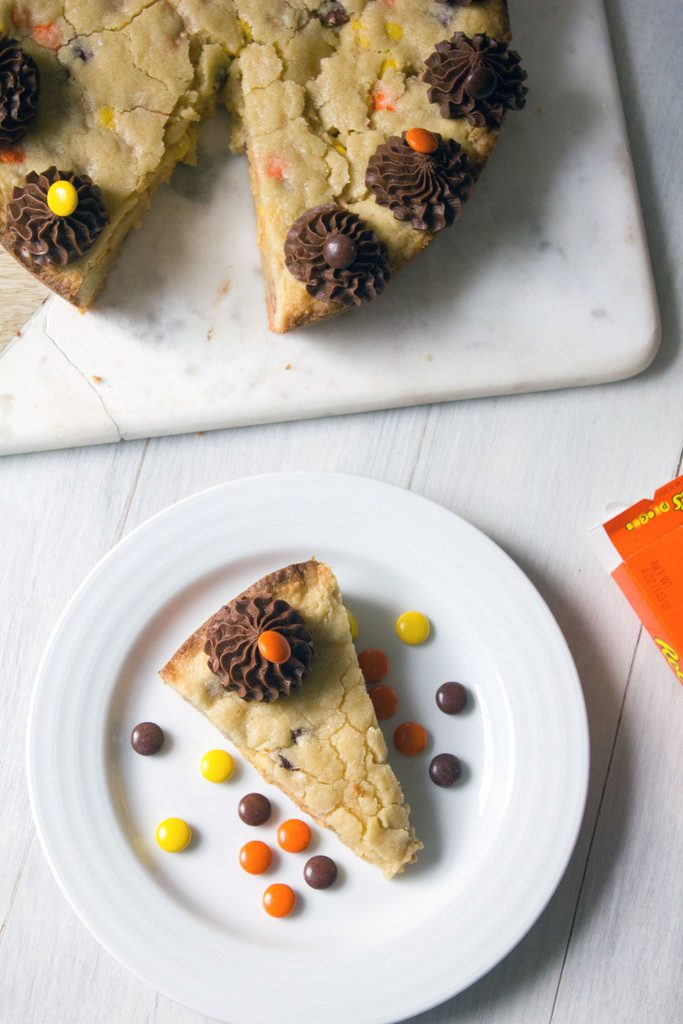 Bird's eye view of a slice of Reese's Pieces cookie cake on a white plate with rest of cookie cake on a platter