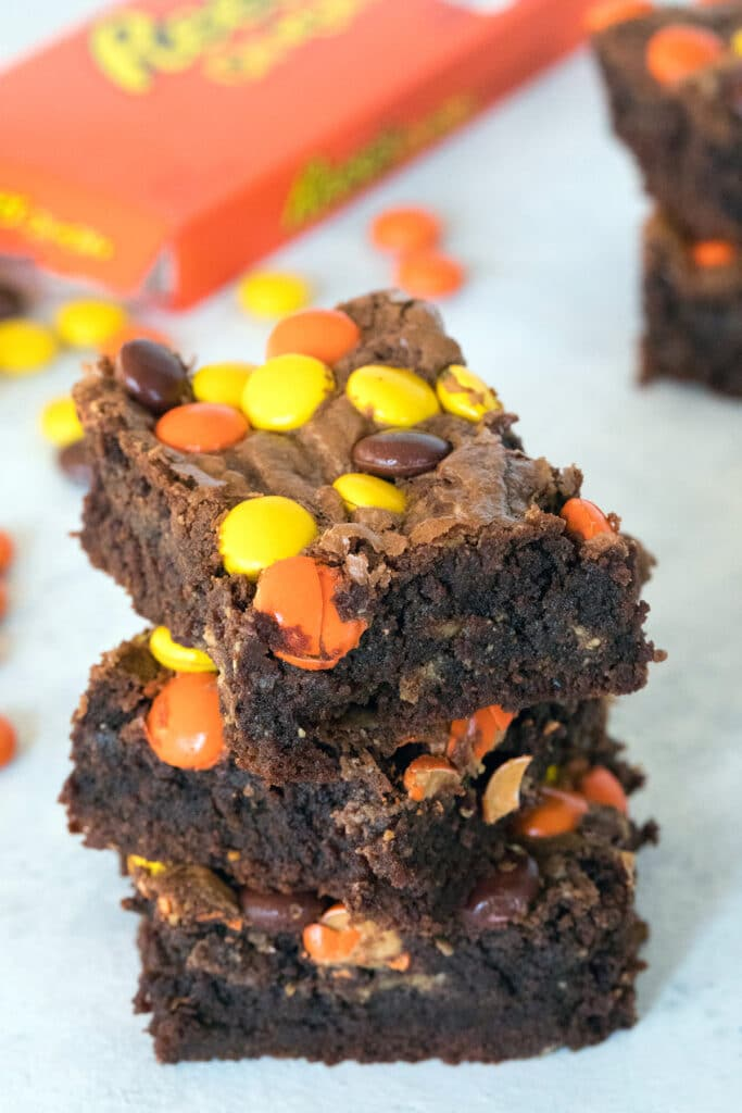 Head-on view of a stack of three Reese's Pieces peanut butter brownies with box of Reese's Pieces in the background
