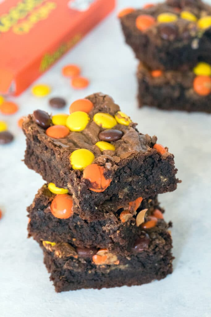 Overhead view of stack of three Reese's Pieces peanut butter brownies with Reese's Pieces and more brownies in background