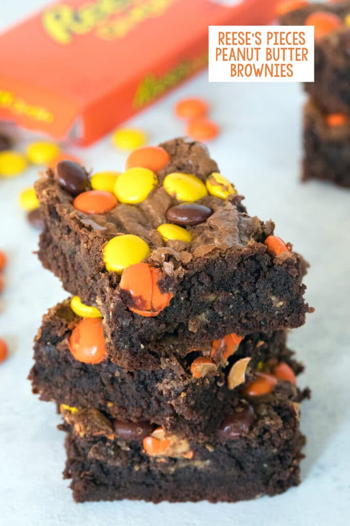 Head-on view of a stack of three Reese's Pieces peanut butter brownies with box of Reese's Pieces in the background with recipe title at top
