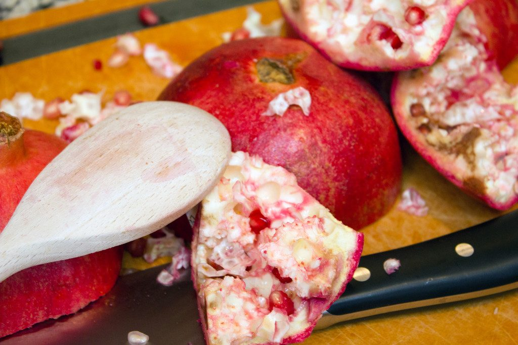 Cutting board with pomegranate pieces scattered around, along with a knife, and wooden spoon