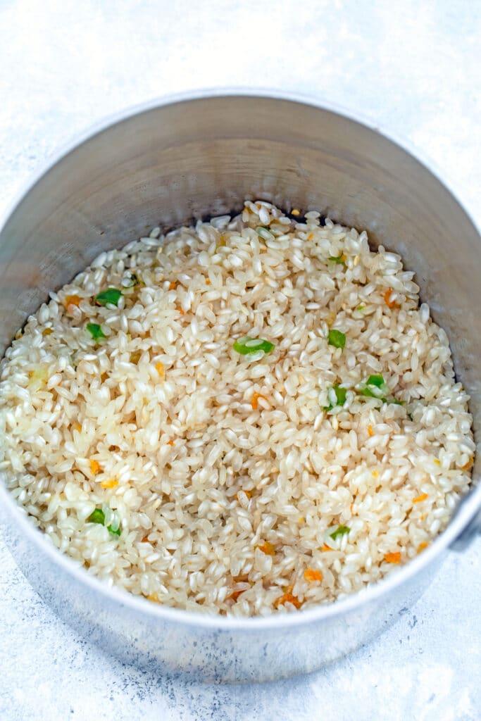 Overhead view of arborio rice, garlic, and jalapeño in saucepan