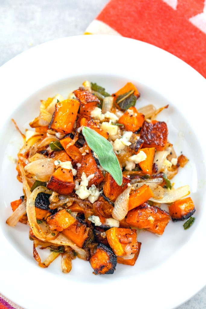 Overhead view of a white plate with roasted butternut squash with caramelized onions and gorgonzola with crispy sage