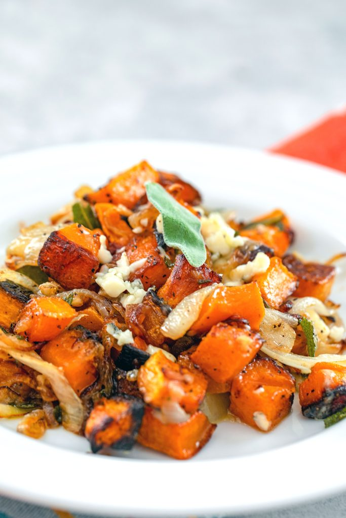 Head-on view of roasted butternut squash with caramelized onions and gorgonzola with crispy sage on a white plate