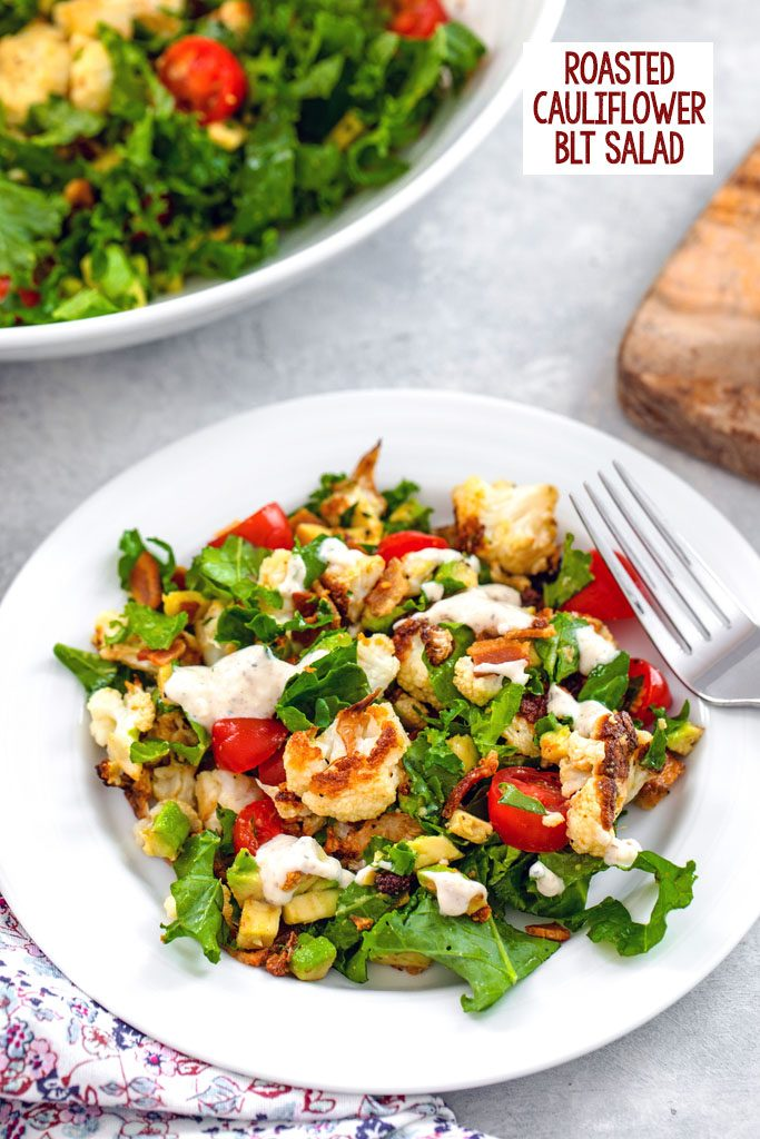 Overhead closeup view of a white bowl of roasted cauliflower BLT salad with a large bowl in the background and recipe title at top