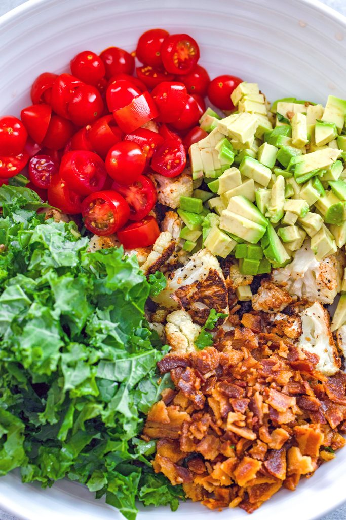 Overhead view of ingredients for roasted cauliflower BLT salad in a bowl including roasted cauliflower, chopped kale, cherry tomatoes, diced avocado, and crumbled bacon