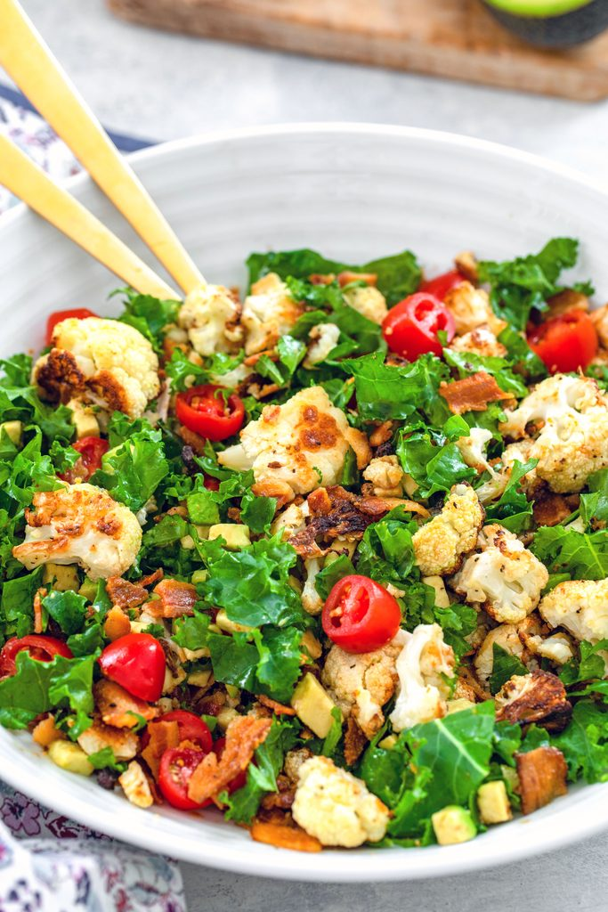 Head-on view of a large serving bowl of roasted cauliflower BLT salad with gold serving pieces
