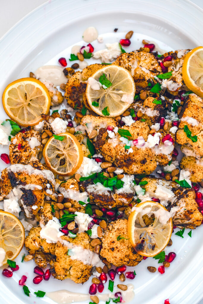 Bird's eye view of roasted cauliflower salad on a white platter topped with roasted lemons, pomegranate arils, crumbled feta, pine nuts, parsley, and tahini dressing