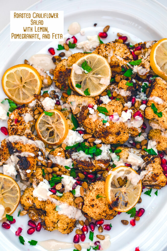 Bird's eye view of roasted cauliflower salad on a white platter topped with roasted lemons, pomegranate arils, crumbled feta, parsley, and tahini dressing with recipe title at top
