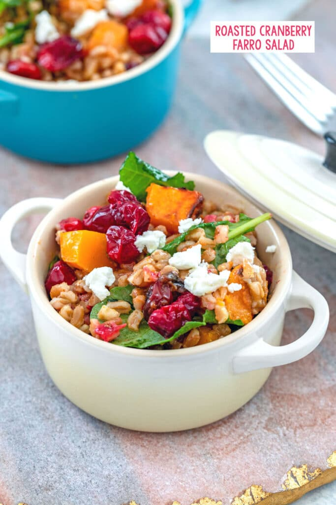 View of a small cocotte filled with cranberry farro salad with butternut squash, baby kale, and goat cheese, with another cocotte in background and recipe title at top