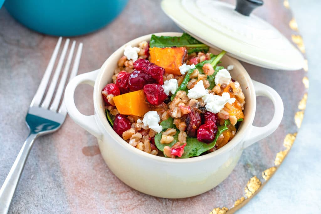 Landscape overhead view of a white cocotte filled with cranberry farro salad with butternut squash, baby kale, and goat cheese on a pink and gold platter with fork