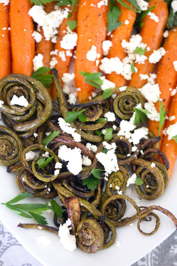 Closeup of roasted fiddleheads topped with feta cheese and parsley