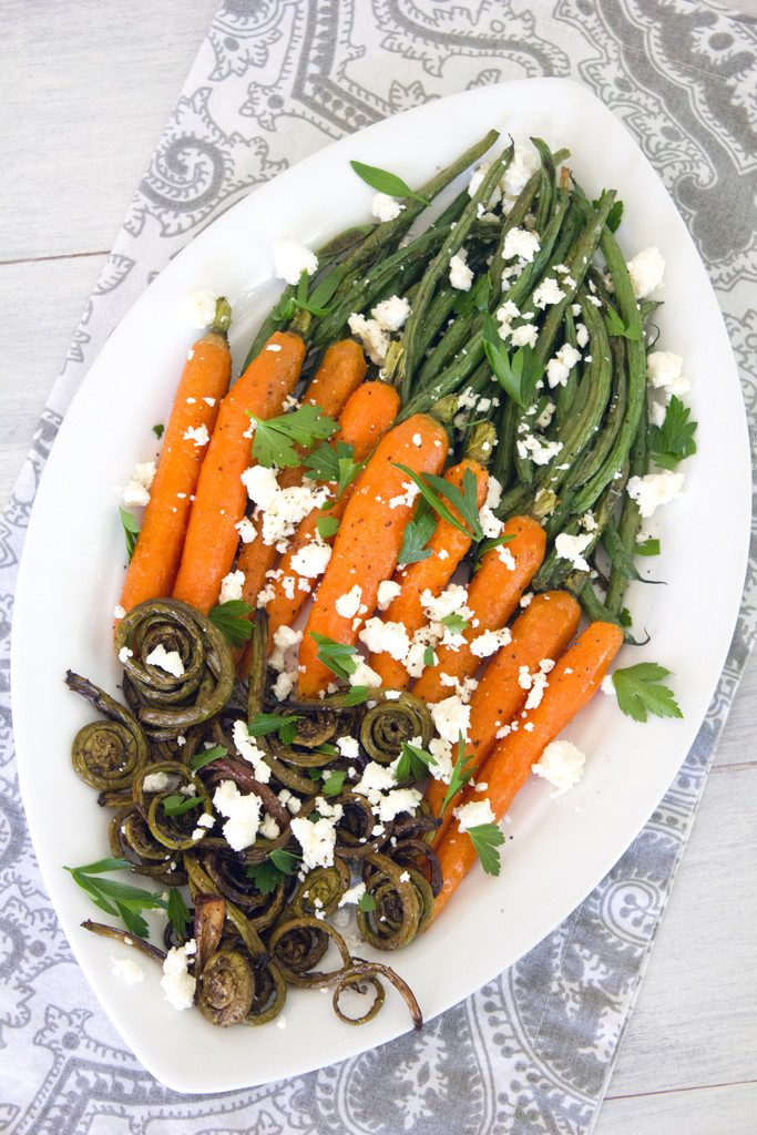 Bird's eye view of white platter with roasted fiddleheads, carrots, and haricot vert with feta cheese and parsley on a grey and white napkin