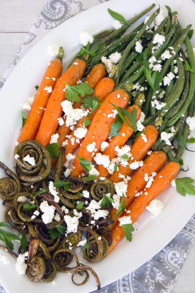 Overhead view of white platter with roasted fiddleheads, carrots, and haricot vert topped with feta cheese and parsley