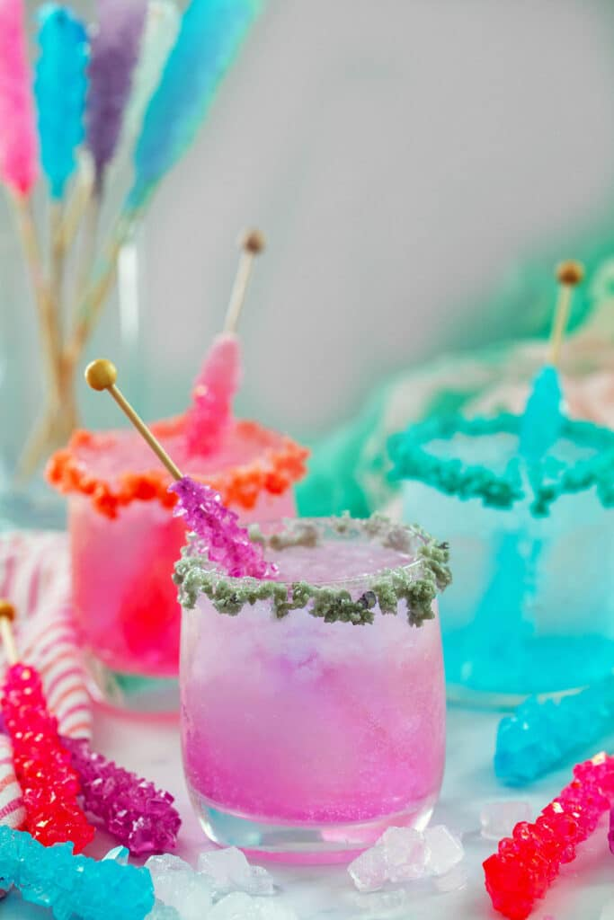 Head-on view of a purple rock candy cocktail with Pop Rocks garnish with more cocktails and rock candy in background