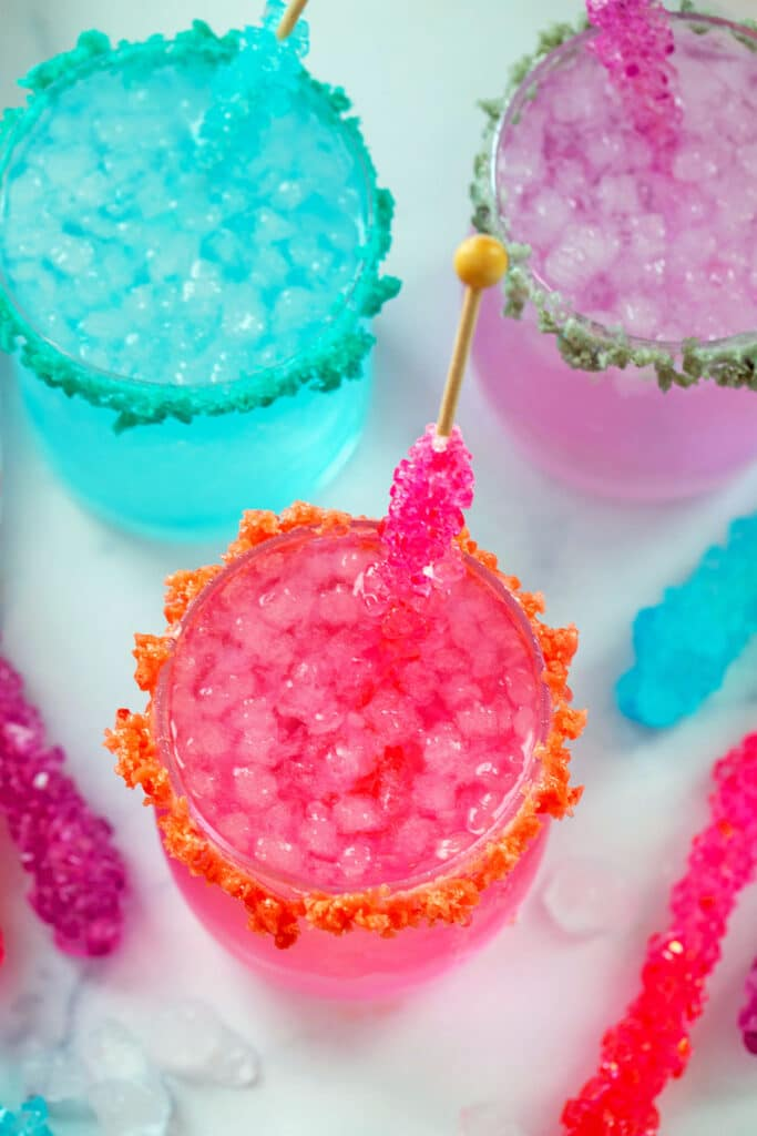 Overhead view of three brightly colored glasses of rock candy cocktail with rock candy sticks and more candy all around