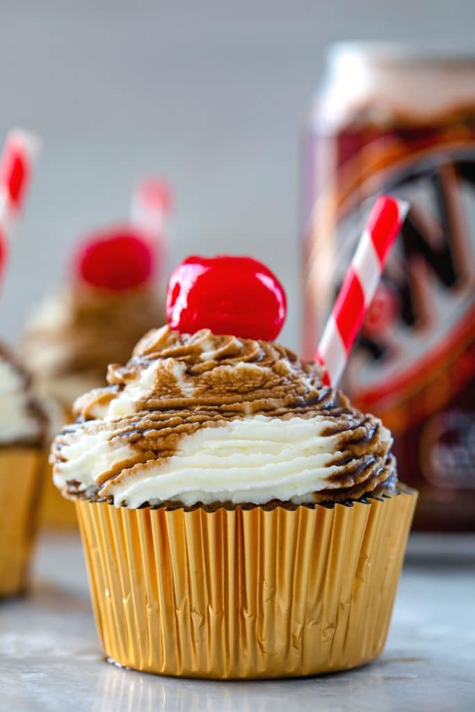 Close-up head-on photo of root beer float cupcake with red and white striped straw and cherry with can of root beer in the background