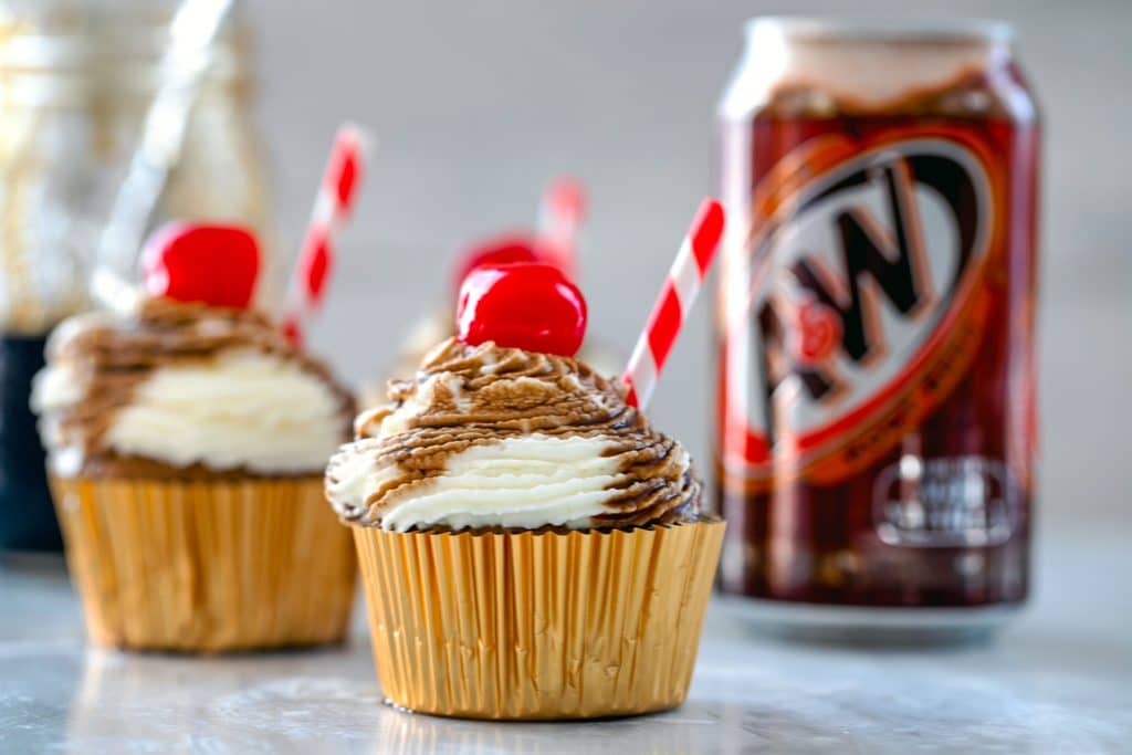 Landscape photo of root beer float cupcakes with red and white straws and cherries with jar of root beer syrup and can of root beer in the background