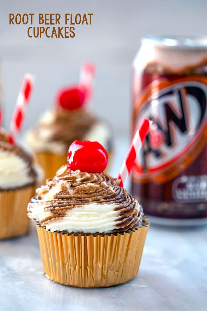 "Head-on view of root beer float cupcake with red and white straw and cherry with other cupcakes and a can of root beer in the background and ""Root Beer Float Cupcakes"" text at top"