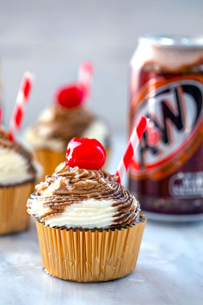 Head-on view of root beer float cupcake with red and white striped straw and cherry with other cupcakes and a can of root beer in the background