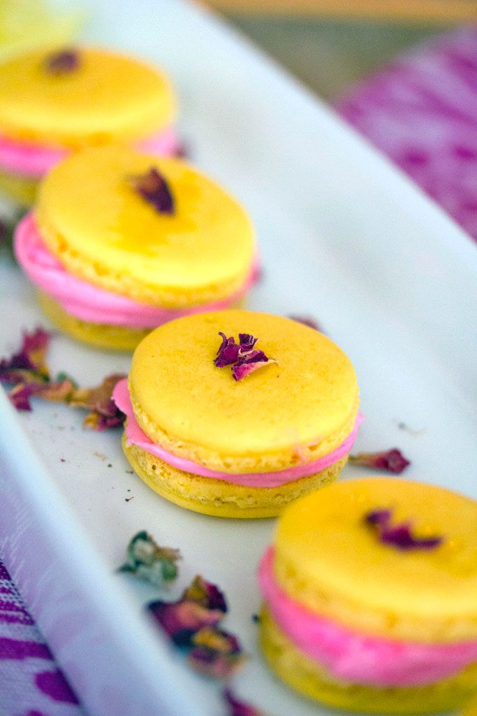 Overhead view of lemonade macarons with pink rose buttercream lined up on a white platter, each topped with rosebuds and rosebuds scatters around platter