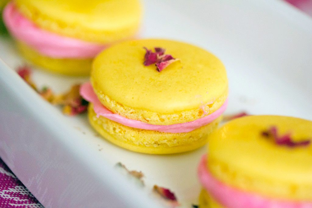 Three lemonade macarons with pink rose buttercream on a white platter with rosebuds scatted around