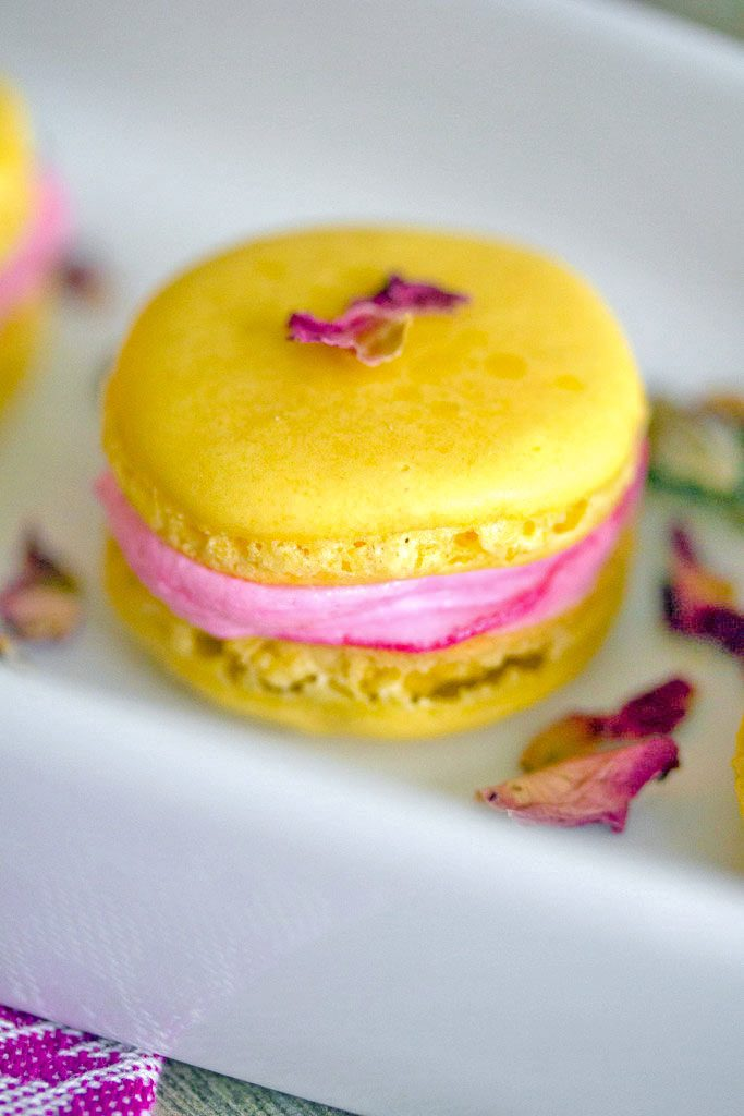 Head-on view of a single yellow lemonade macaron with pink rose buttercream, topped with pink rosebuds on a white platter