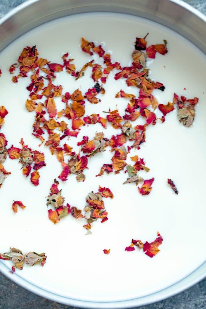 Rose petals sprinkled over milk in saucepan