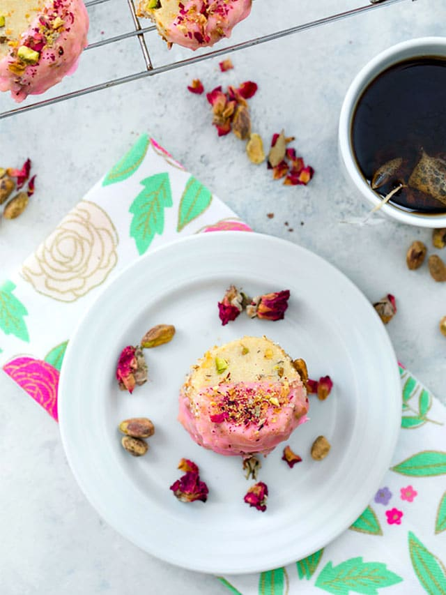 Bird's eye view of rose pistachio shortbread cookies on both a plate and baking rack with a rose tea towel, cup of tea, and rose petals scattered around