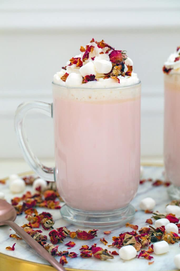 Head-on view of a big mug of pink colored rose white hot chocolate topped with whipped cream, mini marshmallows, and rose petals with rose petals all around