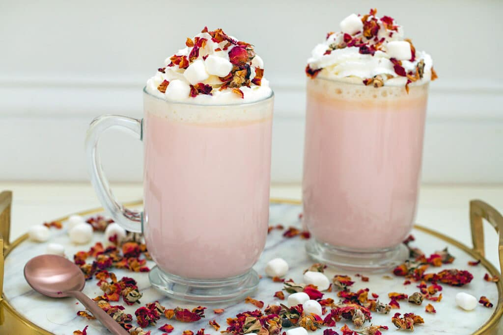 Landscape view of two large mugs of pink colored rose white hot chocolate on a marble and gold platter with rose petals and mini marshmallows scattered everywhere